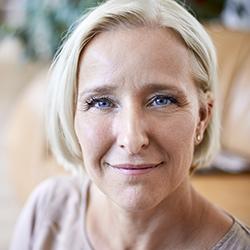 Nahaufnahme einer Frau mittleren Alters mit blauen Augen und blonden Haaren